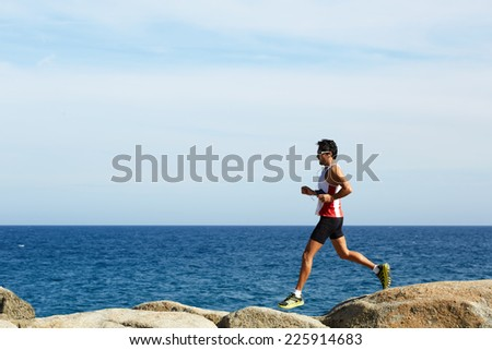 Young athlete running fast jumping on rocks with beautiful sea horizon on background - stock photo
