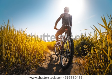 Young athlete standing with bicycle on the meadow with yellow lush grass - stock photo