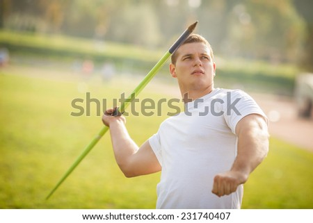 Young athlete throwing the javelin. - stock photo