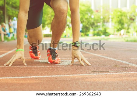 Young athlete waiting at the starting line on the race track. Image of a male runner training hard for a running competition with retro filter. Doing sport for getting in shape and keeping fit concept - stock photo