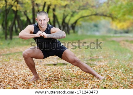 young athlete with sporty physique engaged charging Outdoors - stock photo