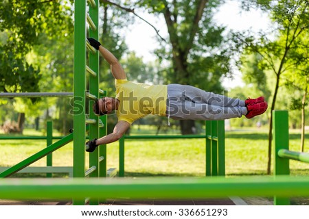 Young athlete working out in an outdoor gym, doing street workout exercises - stock photo
