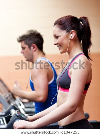 Young athletes exercising on a running machine with earphones in a fitness center - stock photo