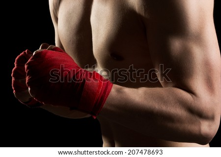 Young, athletic built man on a kick boxing training isolated on a black background - stock photo