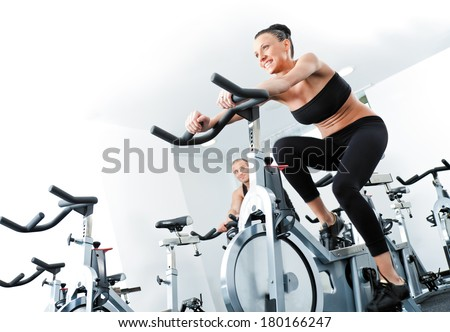 Young athletic female spinning veloargometers in gym, male behind - stock photo