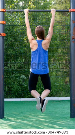 Young athletic girl hanging on the bar, the view from the back - stock photo