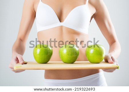 Young athletic girl holding an apple in front of his flat stomach on a white background - stock photo