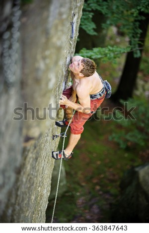 Young athletic man climbing on cliff wall with rope engaged. Outdoor summer day - stock photo