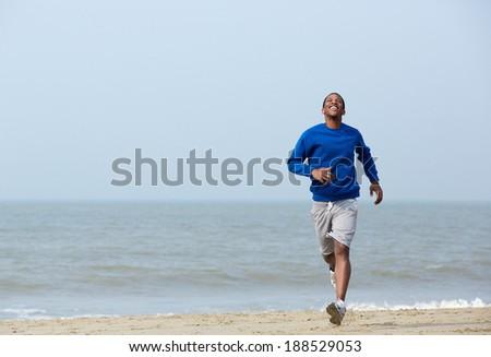 Young athletic man enjoying a jog at the beach - stock photo