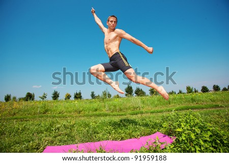young athletic man jumping on grass - stock photo