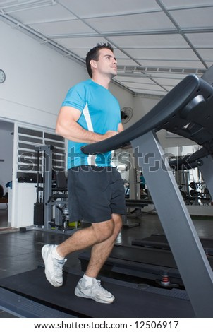 Young athletic man running on a treadmill at the gym - stock photo
