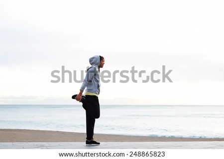 Young athletic man stretching his legs before a morning run, full length of a young jogger stretching in the morning on seaside - stock photo