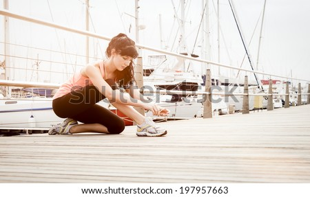 Young athletic runner tying shoe laces on wooden deck - stock photo