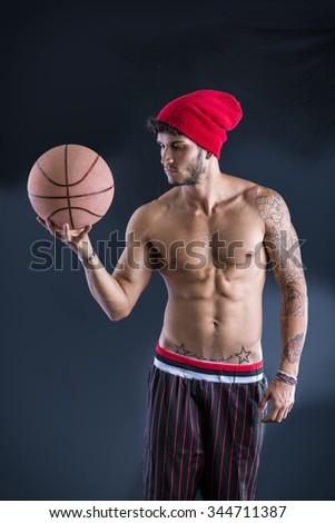 Young athletic shirtless man on dark background holding basketball ball, looking to a side - stock photo