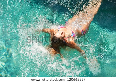 Young athletic woman diving into a blue swimming pool, splashing water around her. - stock photo