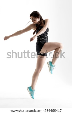Young athletic woman doing exercise in sportswear jumping in the air - stock photo