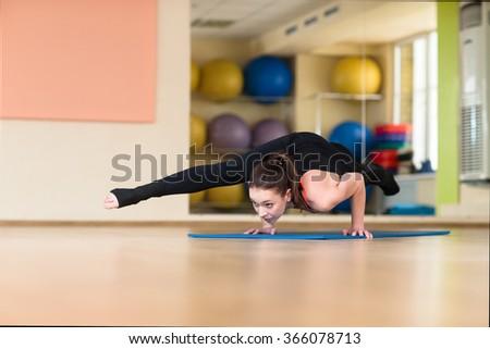 Young athletic woman doing yoga pose in Bakasana Crane Pose, Crow Pose. Indoor gym. - stock photo