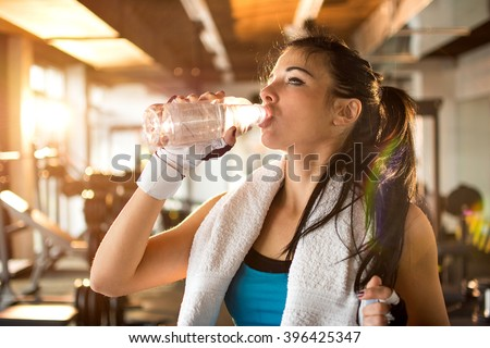 Young athletic woman drinking water in gym. - stock photo