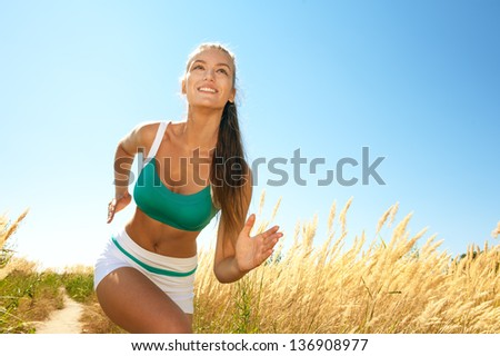 Young athletic woman running outdoors in sunny day - stock photo