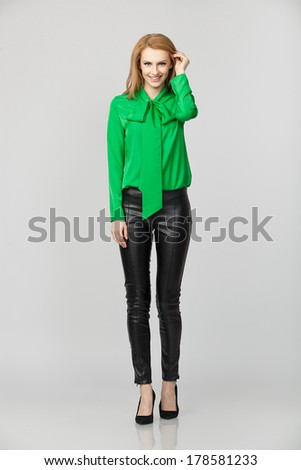 young atractive blonde woman in green shirt smiling - stock photo
