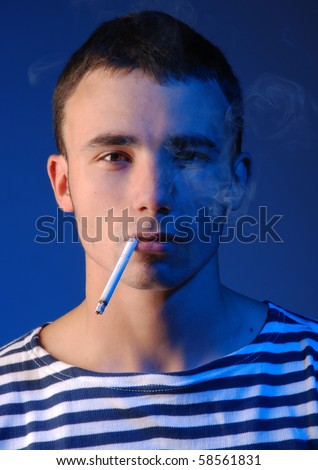 Young atractive man in striped jersey smoking - stock photo