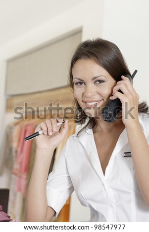 Young attendant using the telephone in a fashion store. - stock photo