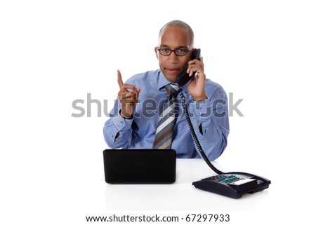 Young attractive African-American businessman in office at his desk, in front of a laptop and talking to telephone, explaining. Studio shot. White background - stock photo