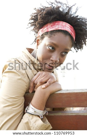 Young attractive african american woman being thoughtful while sitting on a bench in a city park. - stock photo