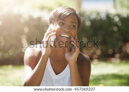 Young attractive African woman with short haircut talking on cell phone to her friend, looking happy, sitting on the grass in the city park, touching her chin. Human face expressions and emotions - stock photo