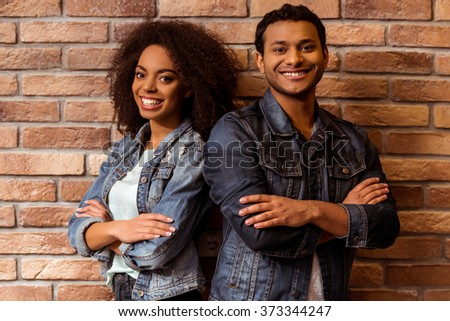 Young attractive Afro-American couple in jeans jackets looking in camera and smiling while standing back to back against brick wall - stock photo