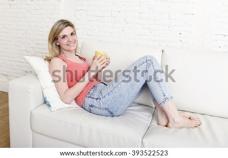 young attractive and blond hair woman holding cup of coffee lying on sofa couch at home living room smiling happy and relaxed lifestyle concept - stock photo