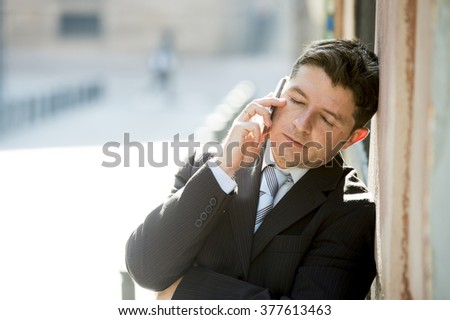 young attractive and busy businessman with closed eyes wearing suit and tie talking business on mobile phone leaning on street wall outdoors in the morning  - stock photo