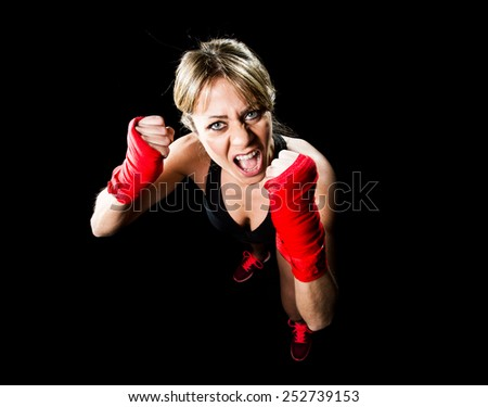 young attractive and sexy girl training boxing with wraps on fists feeling angry in female boxer and fighting woman concept isolated on black background  - stock photo