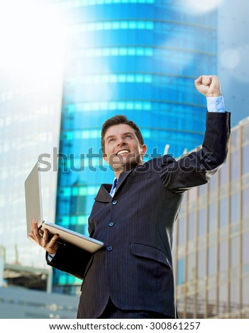 young attractive and successful businessman in suit and tie with computer laptop happy and excited doing victory sign celebrating success outdoor on financial district street - stock photo