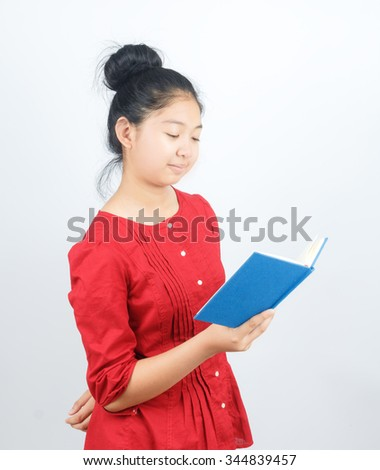 young attractive asian girl who reads a book - stock photo