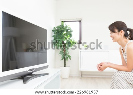 young attractive asian woman watching TV in living room - stock photo