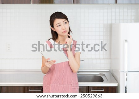 young attractive asian woman who cooks - stock photo