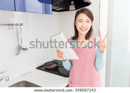 young attractive asian woman who cooks while watching tablet pc - stock photo