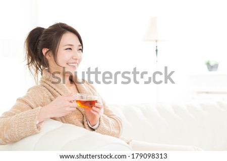 young attractive asian woman who drink tea - stock photo