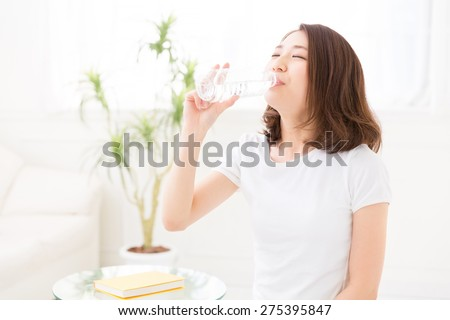 young attractive asian woman who drinks water - stock photo