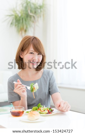 young attractive asian woman who  eats - stock photo