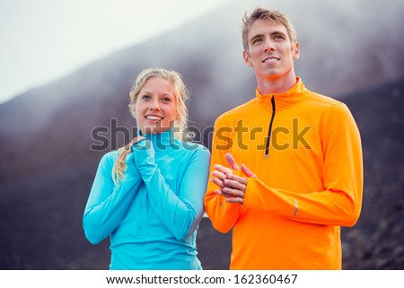 Young attractive athletic couple, wearing sporty cloths on trail outside in nature, relaxing after workout - stock photo