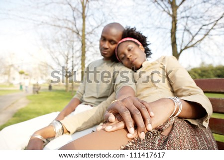 Young attractive black couple sitting down on a bench in the park while visiting the Tower of London, holding hands. - stock photo