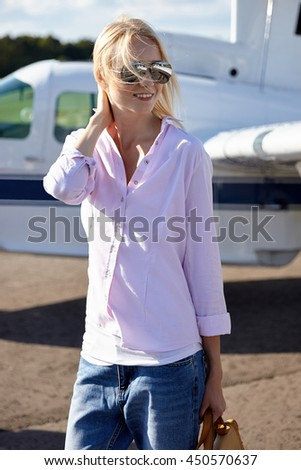 Young attractive blond girl with luggage posing at the aircraft. Concept is traveling on vacation. Models in mirrow sunglasses and classic blue jeans. - stock photo