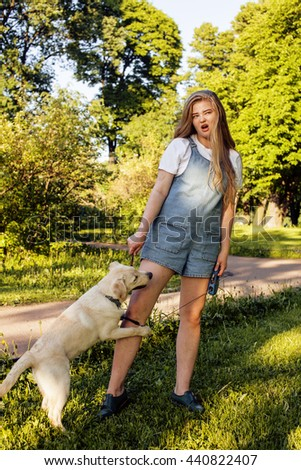 young attractive blond woman playing with her dog in green park at summer, lifestyle people concept - stock photo