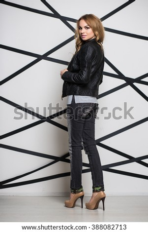 Young attractive blond woman wearing black jacket and jeans - stock photo