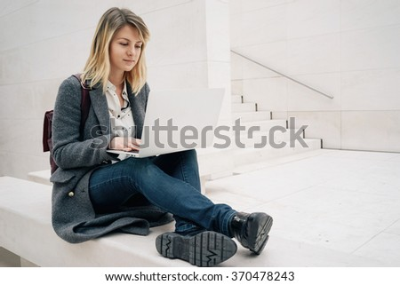 young attractive blonde female student using laptop computer while sitting on the stone bench. copy space area for your text message or content - stock photo