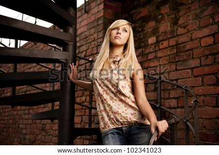 Young attractive blonde on stairs - stock photo