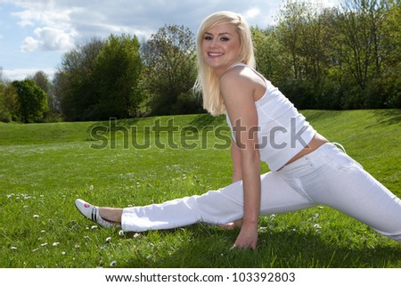 Young attractive blonde stretching outside on a field - stock photo