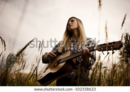 Young attractive blonde with a guitar on meadow - stock photo